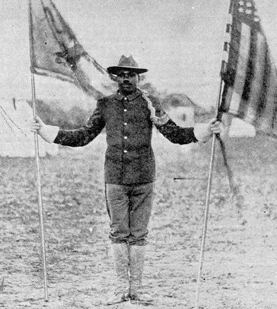 A soldier standing at attention and holding two flags on poles