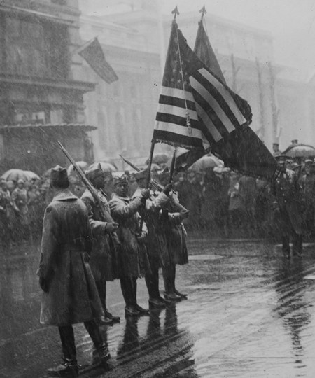 Soldiers holding flags at attention while several others look on all around them