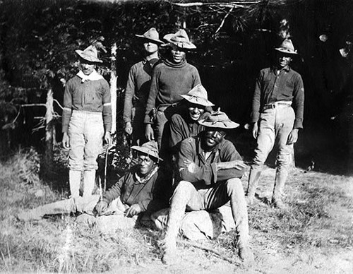 Four soldiers standing and two sitting posing for a photo in front of trees