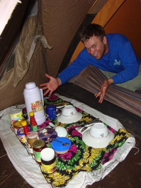 Nathan King camping in a tent with a full supply of food