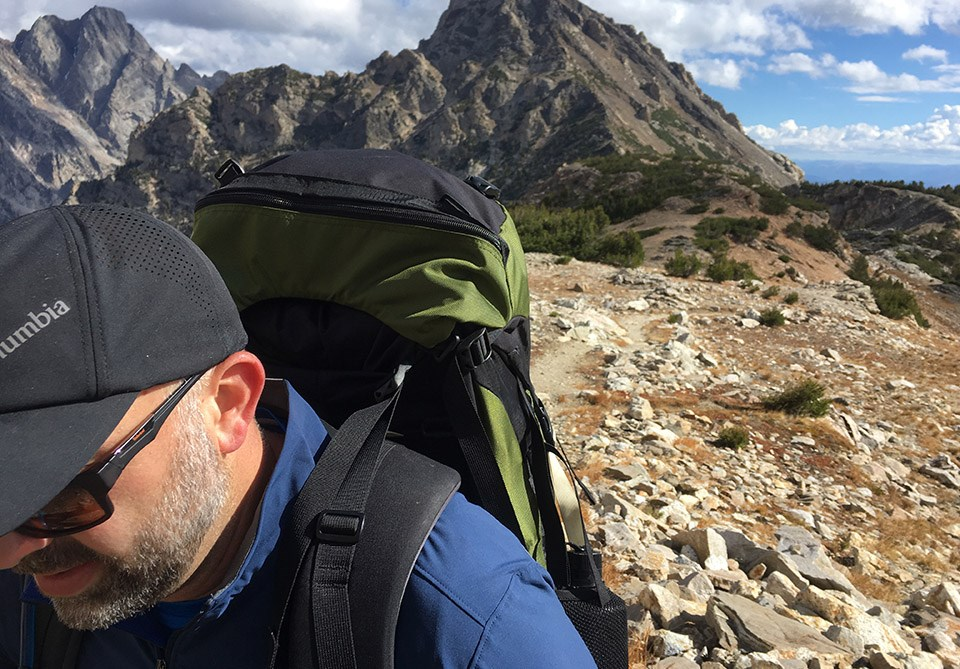 David Restivo hiking with mountains in the background