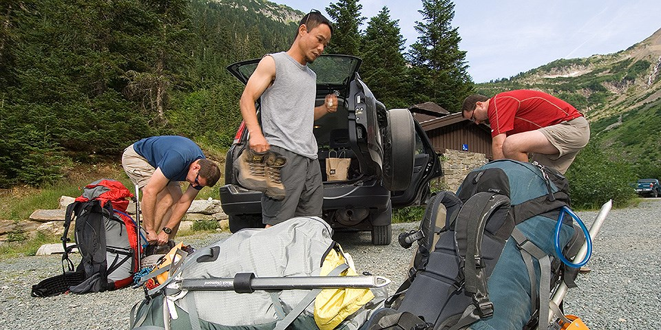 Three men unload backpacks from a car