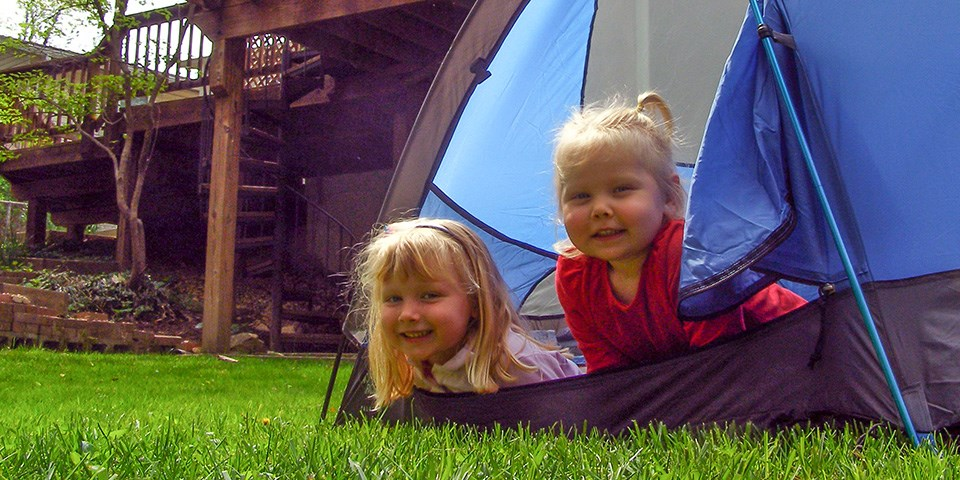 Two children peeking out of their tent in the backyard
