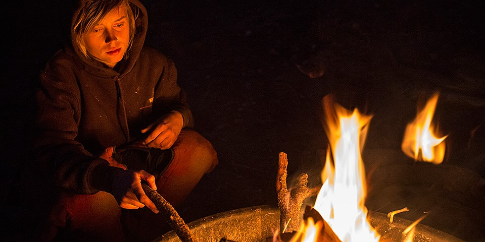 A youth sits next to a campfire