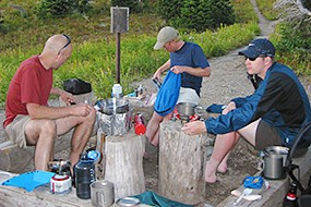Three men sit in a backcountry food preparation area cooking food