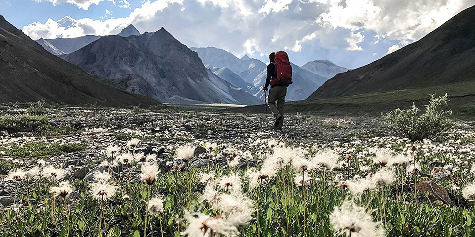 A backpacker walks though a mountain landscape