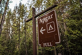 "A brown campground sign with the campground name ""Apgar"" and the word, ""full"""