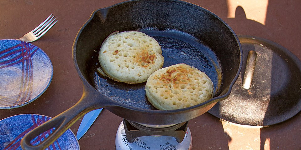 Crumpets cooking in a cast iron skillet