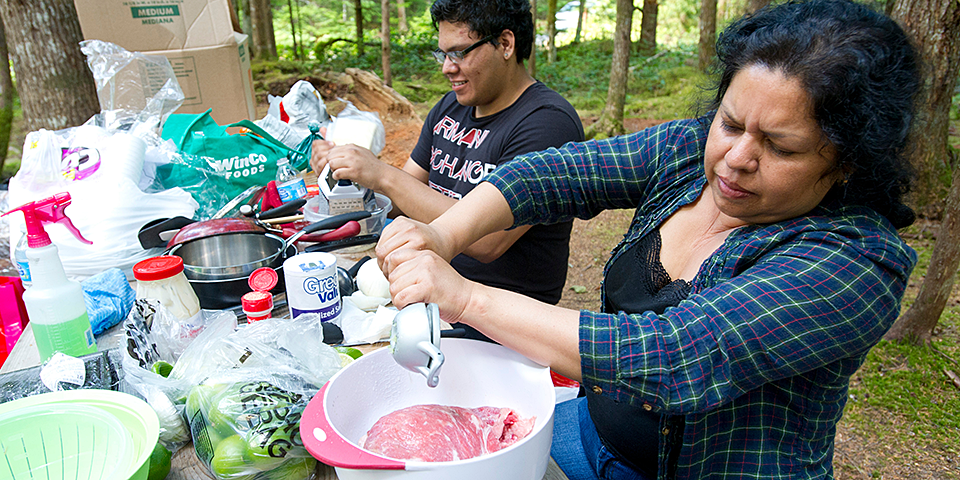 A man and a woman prepare food at a picnic table