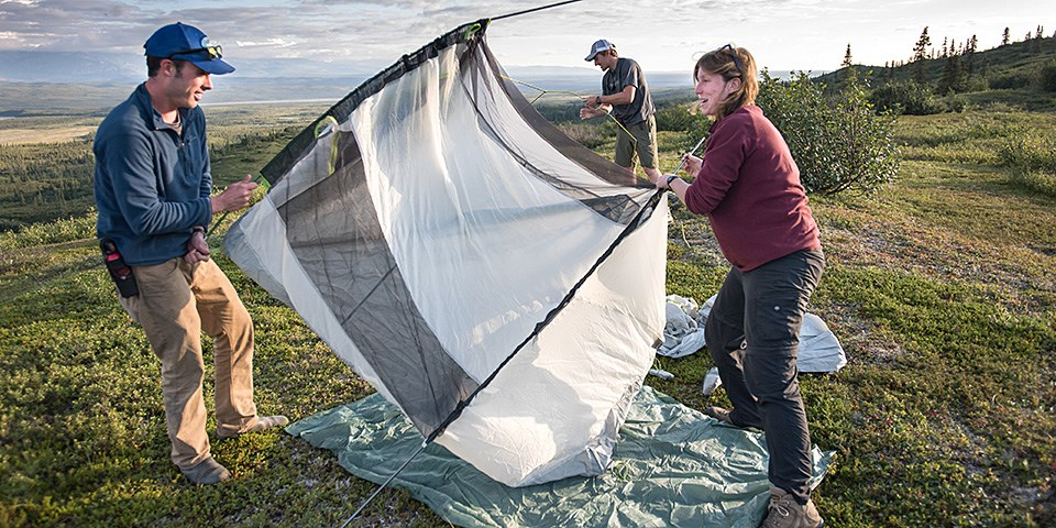 A man and a woman set up a white tent