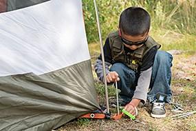 Bir çocuk çadır kurar