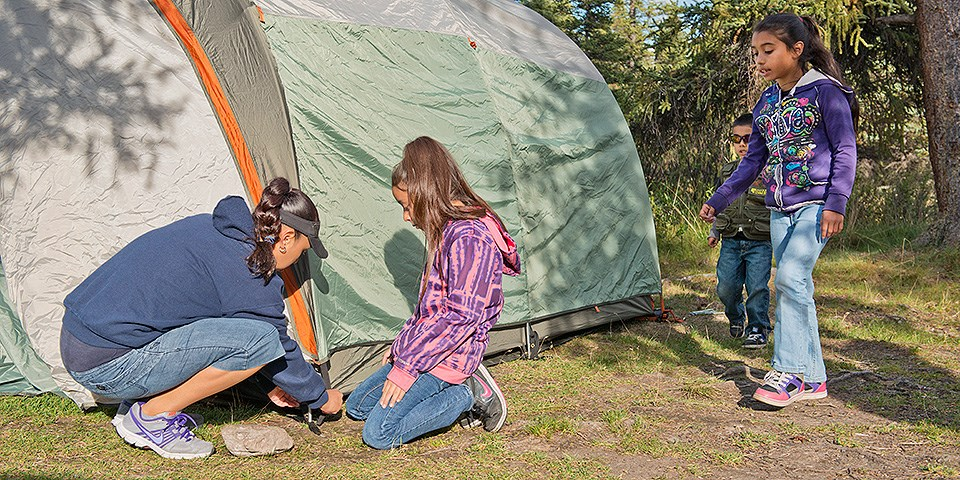 A woman and three kids set up a tent