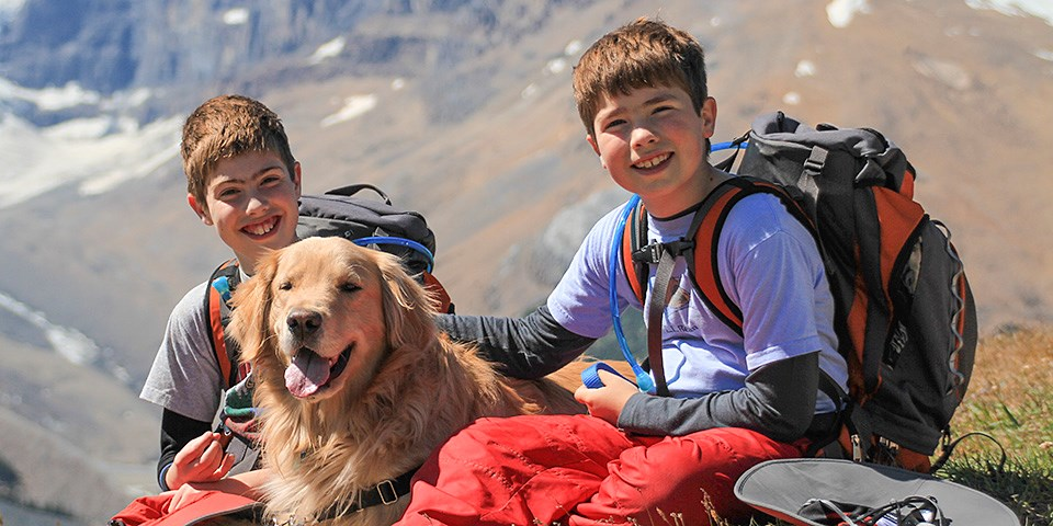 Two kids wearing backpacks sit with a leashed golden retriever dog
