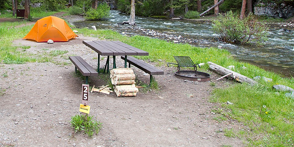A campsite with a site marker, picnic table, fire ring, firewood and an orange tent