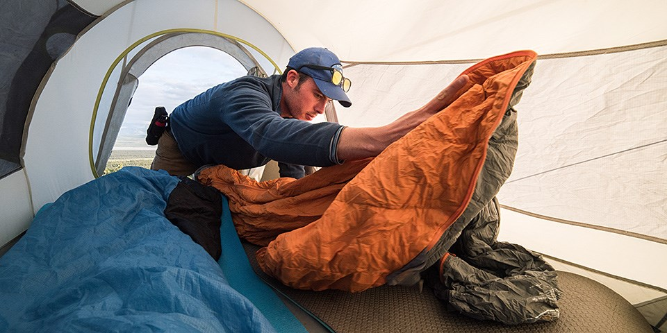 A man unrolls a sleeping bag inside a tent