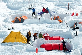 Yellow, orange and red tents are set up in snow with people standing next to them