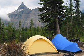 A yellow and blue tent is set up in front of mountains. Rains clouds are present.