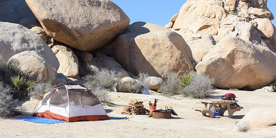 Çölde bir odun yığını, ateş çemberi ve piknik masasının yanında bir test yapılır.