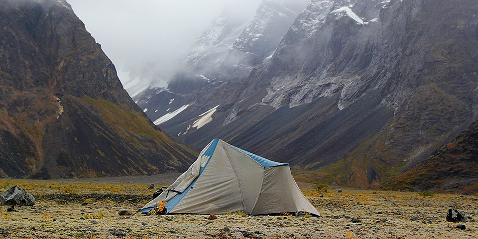 A gray tent is set up in the tundra with snow mountains behind it