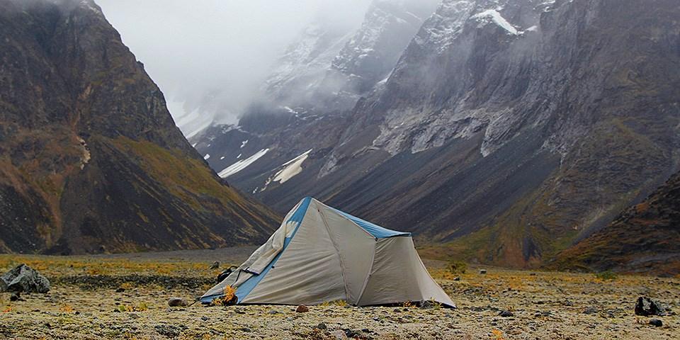 Tundrada arkasında kar dağları olan gri bir çadır kuruluyor