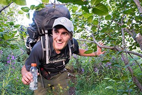 A man walks through thick vegetation carrying a backpack