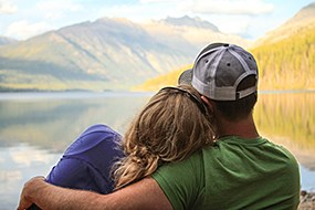 A man wraps his arm around a woman who is resting her head on his shoulder while looking at mountains