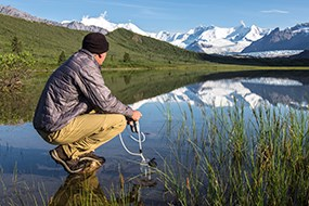 A man kneels to filter water while looking at snow-capped mountains