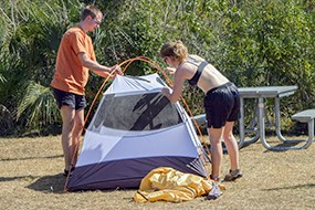 A man and a woman set up a tent in Florida