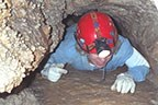 person crawling through cave
