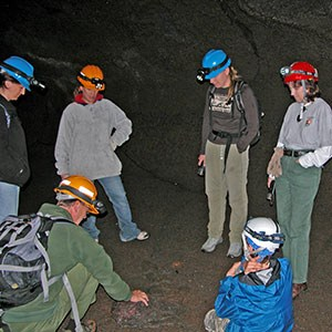 group of people in a cave with ranger