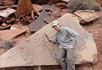 person near fossil trackway on rock slab