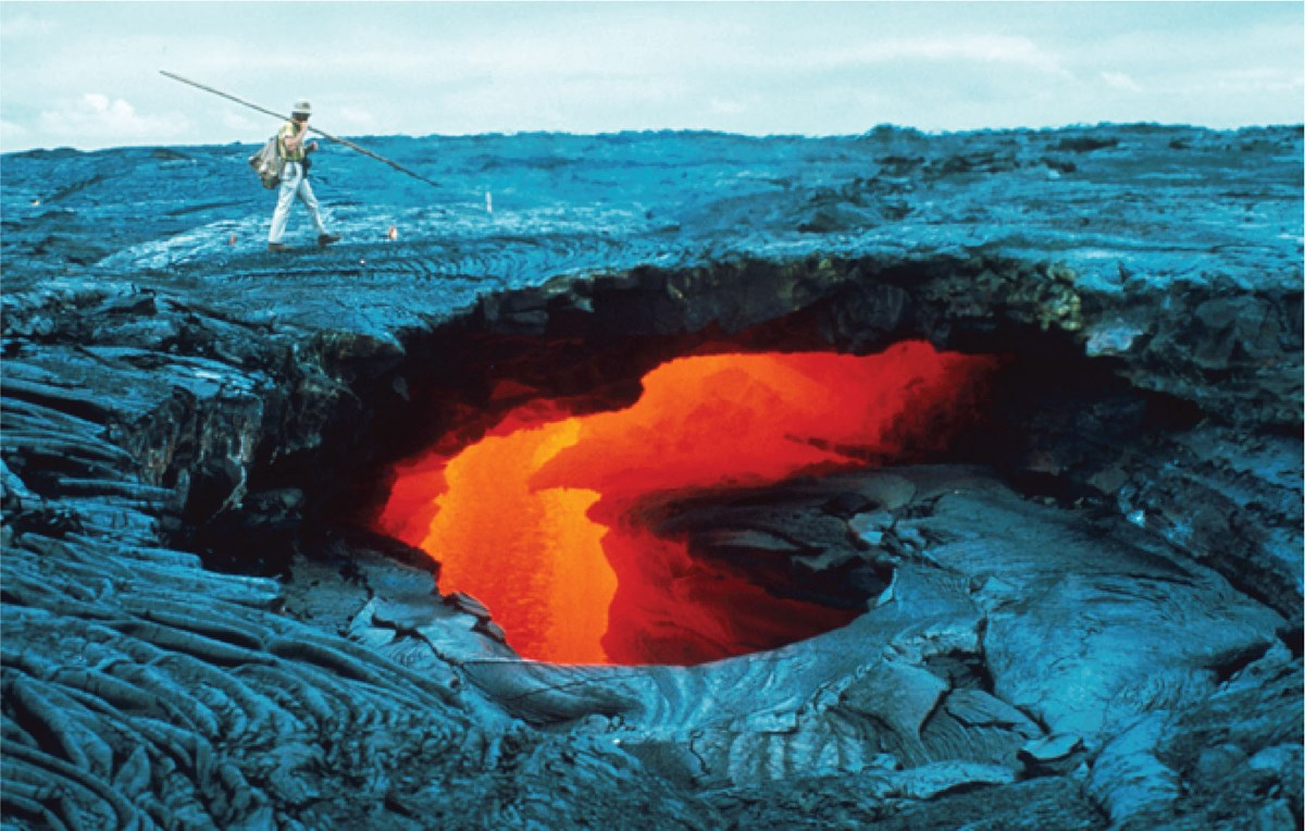 a person walking on hardened lava surface with molten lava visible through a large hole