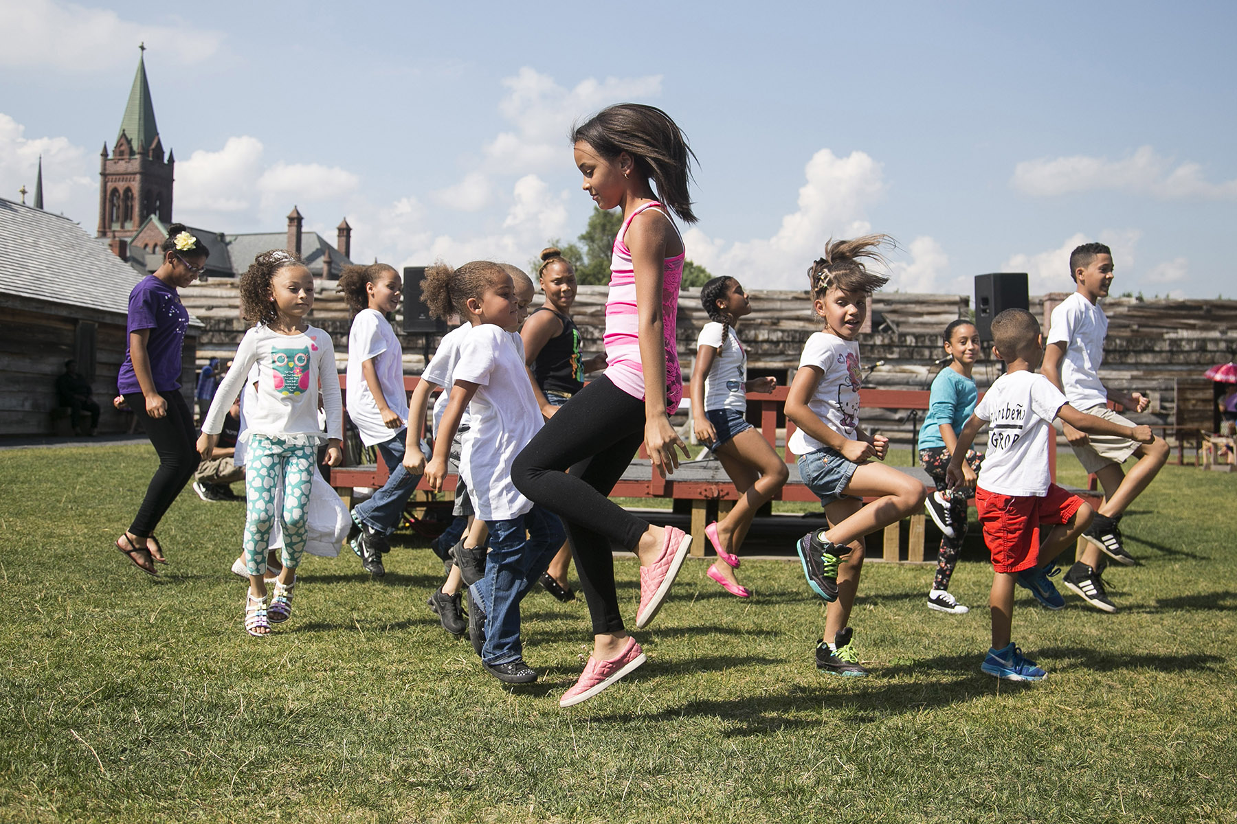 children dancing in grassy area with historic buildings in the background