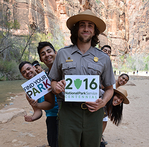 rangers and young people holding centennial logo signs in small canyon