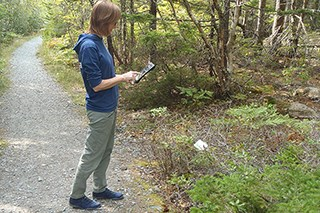 A woman holds an iPad looking at vegetation