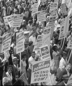 Demonstrators marching in the street holding signs during the March on Washington, August 28, 1963