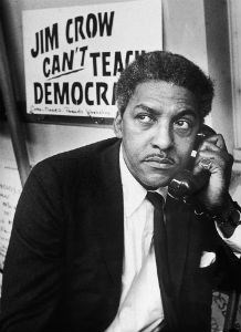 "Bayard Rustin on the telephone while sitting in front of a sign reading ""Jim Crow Can't Teach Democracy."""