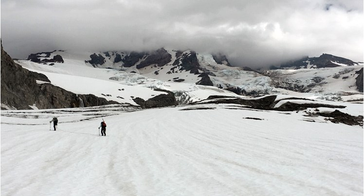 Two researchers walking on glacier with mountain in distance hidden behind clouds