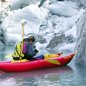 Woman in kayak measuring the end point of a glacier
