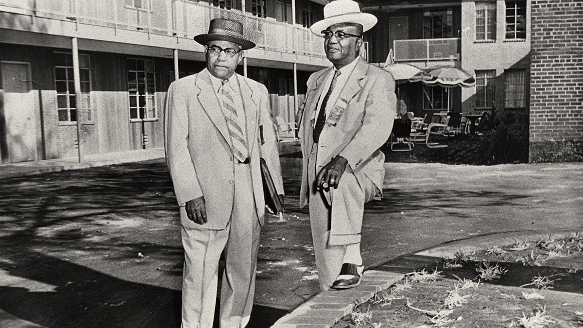 Two African American men in suits and hats in front of a motel