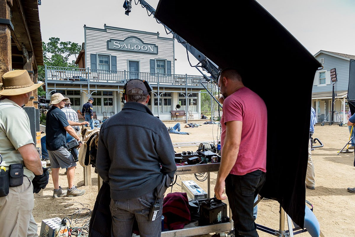 Production crew members with their recording gear in a western town setting