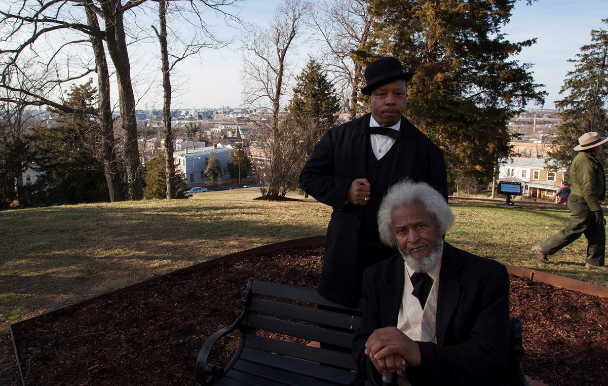 Two African American men in suits, one standing and one seated on a bench, atop a sunny hill with a view of a city beyond.