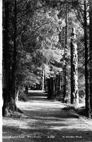 "A black and white photo of ""Lover's Lane,"" where totem poles line a forest walk."