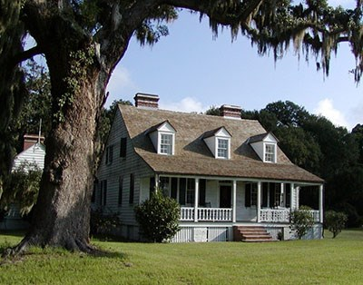 A tall tree with Spanish moss towers over a farmhouse, with a front porch and three dormer windows.