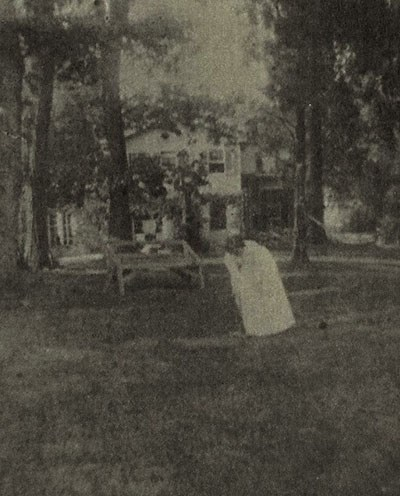 A fuzzy photo of a young girl in a white cress, played croquet in a yard under tall, straight trees.