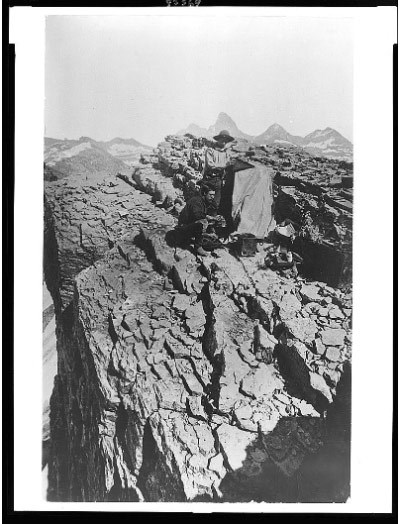 Two men stand with camera equipment on a rocky mountaintop.