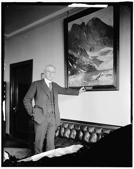 A man in a suit and vest stands in an office next to a leather couch, his arm outstretched to the frame of a painting of a mountain.