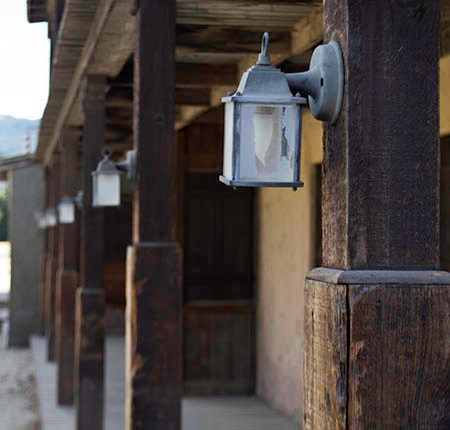 Hanging lanterns are mounted on a row of wooden pillars along a covered porch