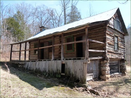 A log cabin with two doors and a long front porch stands on a slope.