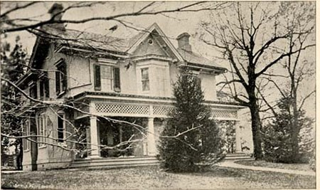 Historic photograph of a two story house, with two young trees at the front and a long front porch.